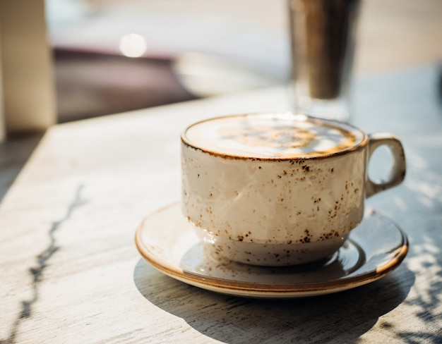 Cappuccino em uma bela xícara de cerâmica está na mesa de um café. o sol da manhã cai sobre a mesa, lindas sombras aparecem. delicioso café da manhã aromático.