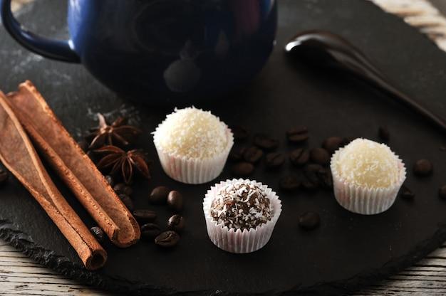 Cappuccino em uma caneca, canela e cupcakes com creme e chocolate