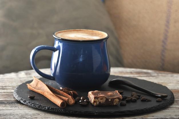 Cappuccino em uma caneca com espuma de leite e canela e chocolate