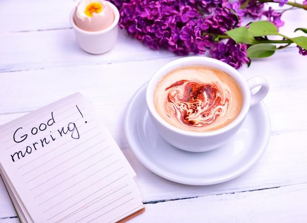 Cappuccino em uma xícara branca, próxima nota com a inscrição bom dia