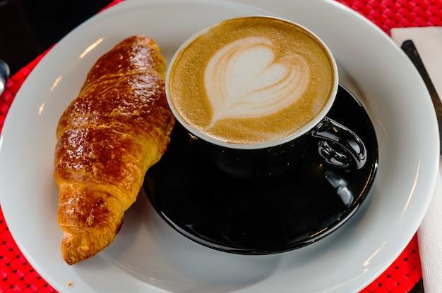 Cappuccino em uma xícara com croissant na mesa.
