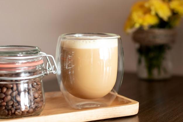 Cappuccino em uma xícara de vidro duplo e frasco com grãos de café na placa de madeira.