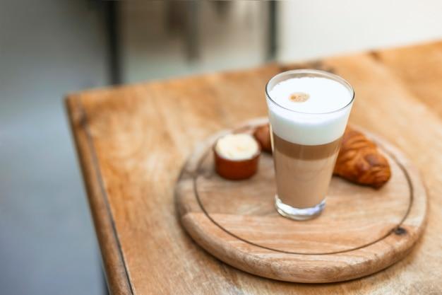 Cappuccino em vidro com croissant na bandeja circular de madeira