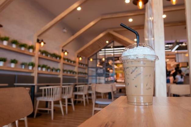 Cappuccino gelado com creme chantilly em copo para viagem na mesa de madeira no fundo do café. Foto Premium