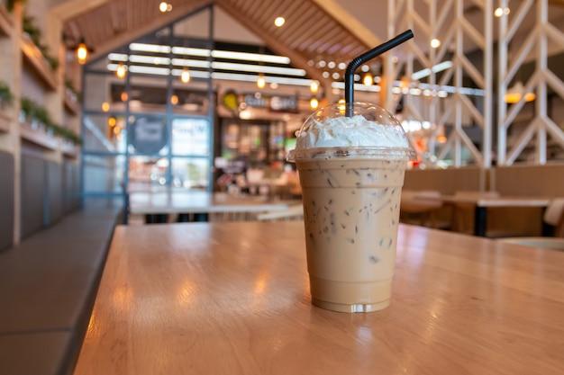 Cappuccino gelado com creme chantilly em copo para viagem na mesa de madeira no fundo do café.
