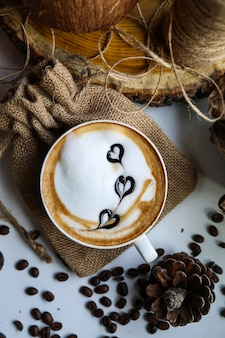 Cappuccino leite foarm feijões arte vista superior