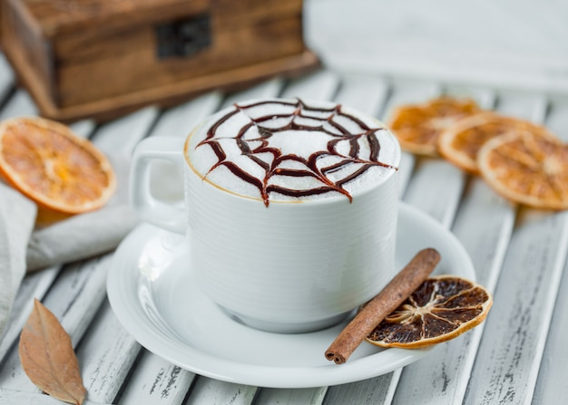 Cappuccino leitoso com calda de chocolate em copo branco com canela e fatias de laranja.