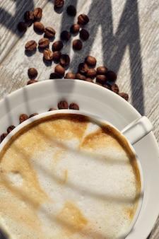 Cappuccino na mesa e grãos de café