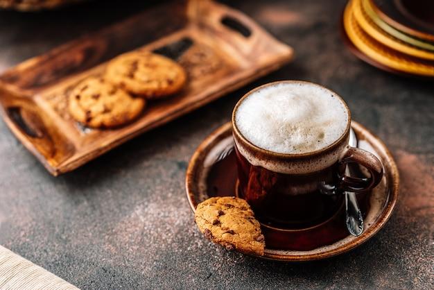 Cappuccino na xícara de café no fundo rústico escuro