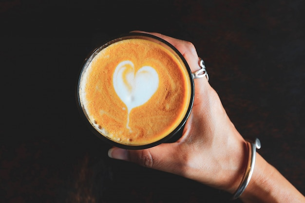 Cappuccino ou café com leite aromático na mão
