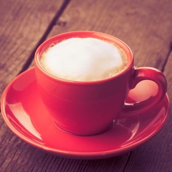 Cappuccino ou café em xícara vermelha - estilo vintage