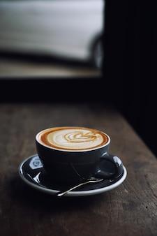 Cappuccino ou café latte art feito com leite na mesa de madeira de uma cafeteria