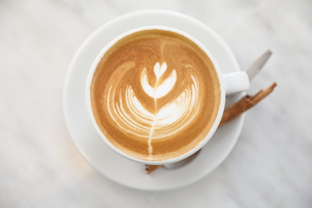 Cappuccino ou latte art café feito de leite na mesa branca na cafeteria