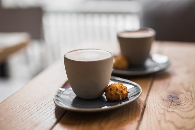 Cappuccino ou latte com espuma espumante com cookie na mesa de madeira