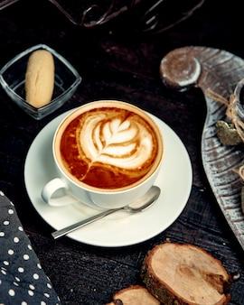 Cappuccino quente com biscoito em cima da mesa