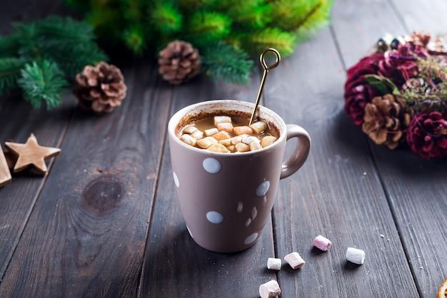 Cappuccino quente com marshmallows em um copo cerâmico com mel e vara de metal mel