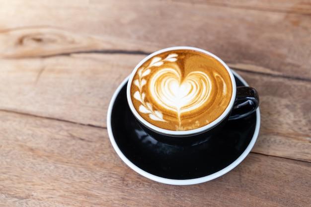 Cappuccino quente do café da arte em um copo no fundo de madeira da tabela com espaço da cópia