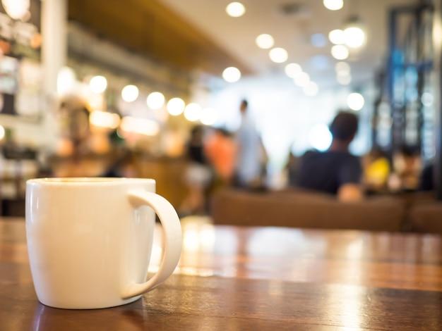 Cappuccino quente do café no copo branco na tabela de madeira e em lojas borradas do café do fundo.
