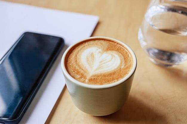 Cappuccino quente na mesa e telefone na mesa de madeira