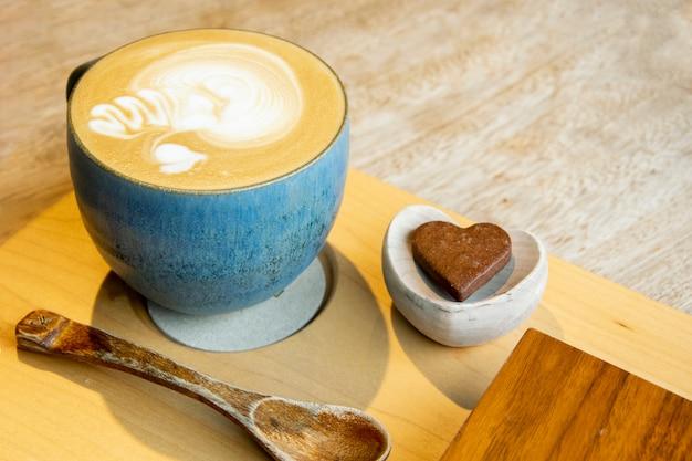 Cappuccino quente no copo na mesa de madeira com copyspace. the latte art on café fundo.