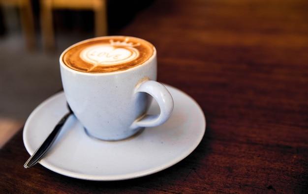 Cappuccino saboroso na mesa de textura de madeira com arte do amor