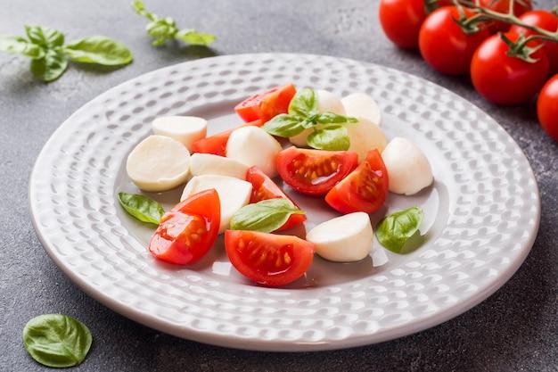 Caprese salada de tomate, mussarela e manjericão em um escuro. cozinha italiana.