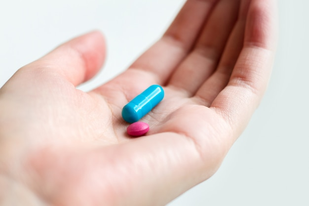Cápsula azul e cor-de-rosa do comprimido na palma fêmea no fundo branco. pílulas antidepressivas na mão feminina.
