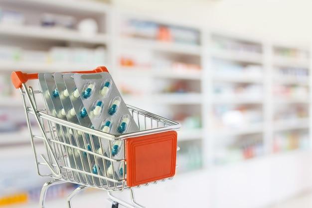 Cápsula de comprimidos médicos no carrinho de compras com prateleiras de farmácias borradas