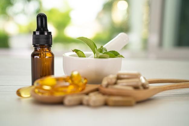 Cápsula de ervas orgânicas de medicina alternativa com vitamina e ômega 3, medicamento mineral de óleo de peixe Foto Premium
