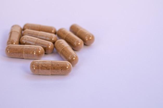 Cápsula de ervas, suplemento nutricional, pílula de vitamina, fitoterapia em fundo branco.