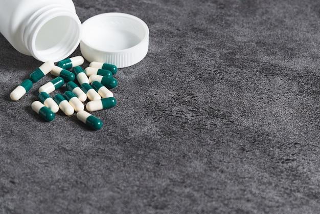 Cápsula de medicamento médico e garrafa de plástico branca no fundo de pedra.