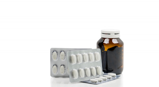 Cápsula de vitaminas em frasco de vidro âmbar com rótulo em branco e suplementos em comprimidos em blister