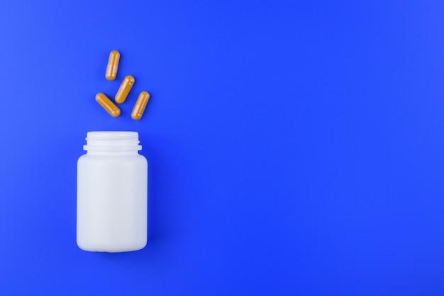 Cápsula do fitoterapia e garrafa branca no fundo, na medicina e na droga azuis.