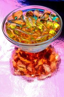 Cápsula ômega 3. em uma tigela de vidro sobre um fundo colorido.