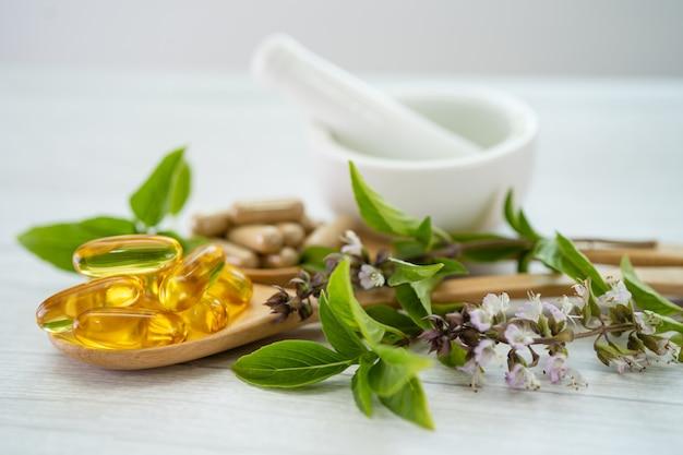 Cápsula orgânica à base de ervas de medicina alternativa com óleo de peixe ômega 3 de vitamina e Foto Premium