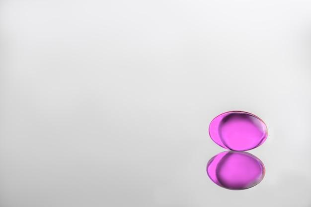 Cápsula rosa gelatinosa sobre um fundo cinza. saúde. vitaminas d, e, ômega 3. copiar espaço