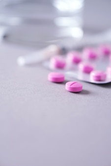 Cápsula rosa, pílulas, vitaminas em fundo cinza. copie o espaço. grupo de drogas, tratamento da gripe fria. tratamento de doenças das mulheres.
