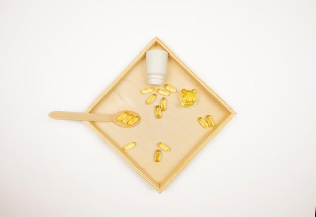 Cápsulas amarelas de ômega 3 repousam em uma bandeja de madeira