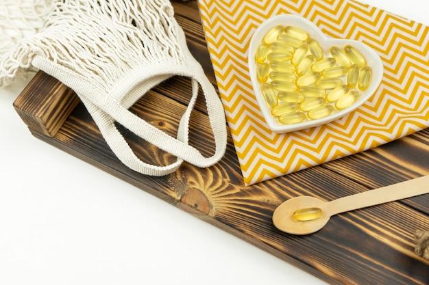 Cápsulas amarelas de ômega 3 repousam em uma placa de cerâmica branca em forma de coração em uma bandeja de madeira
