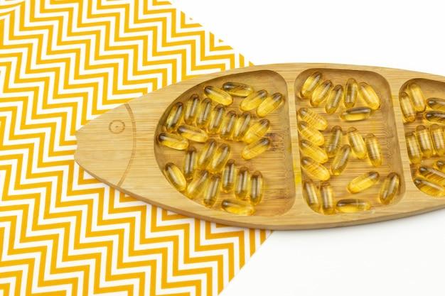 Cápsulas amarelas de ômega 3 repousam em uma placa de madeira na forma de um peixe