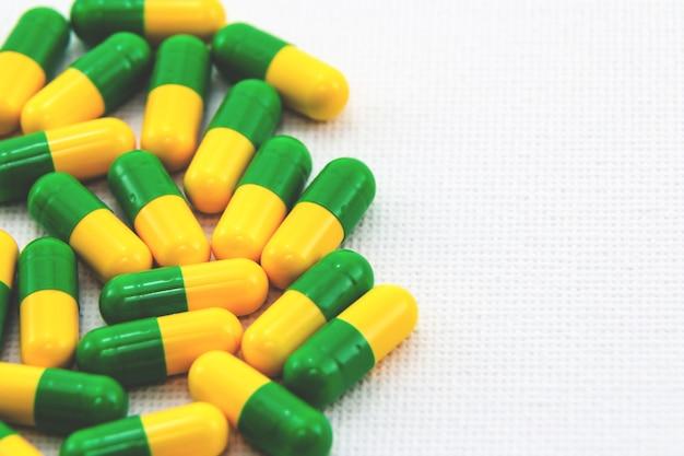 Cápsulas amarelas e verdes em uma superfície branca