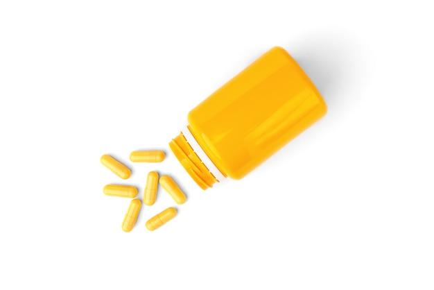 Cápsulas amarelas ou comprimidos isolados no fundo branco.