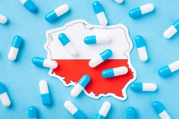 Cápsulas azuis e brancas na bandeira da polónia. propagação de muitas doenças, enfermidades entre a população de um país europeu