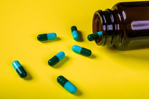 Cápsulas azul esverdeadas caíam de um frasco de remédio marrom. o conceito de farmacologia.
