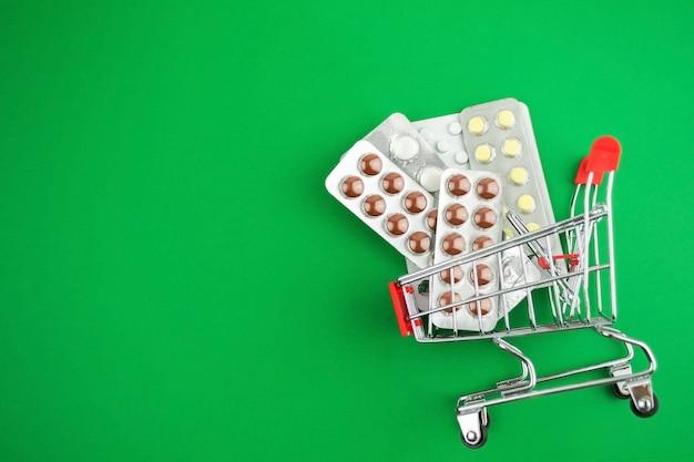 Cápsulas, comprimidos, medicamentos em bolhas em fundo verde no carrinho de compras.