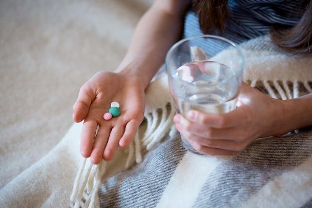 Cápsulas, comprimidos numa mão, um copo de água na outra.