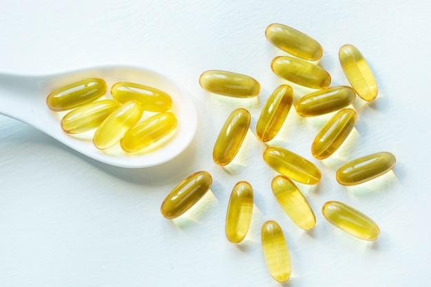 Cápsulas de ácidos graxos ômega 3 em uma colher em um fundo branco close up