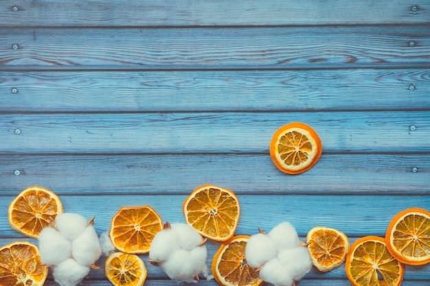 Cápsulas de algodão e laranjas dired na mesa de madeira azul