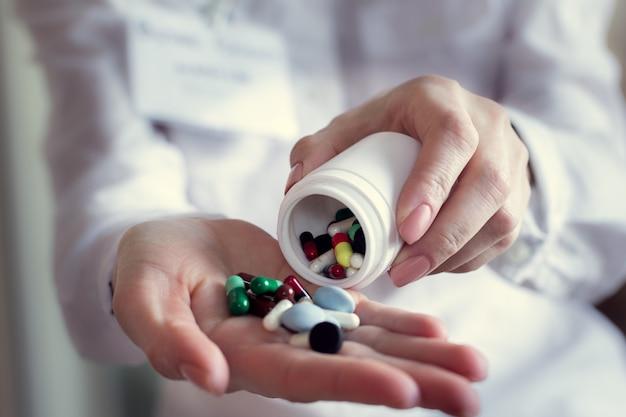 Cápsulas de comprimidos coloridos na mão de um médico