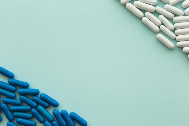 Cápsulas de doces brancos e azuis em frente um ao outro em fundo verde